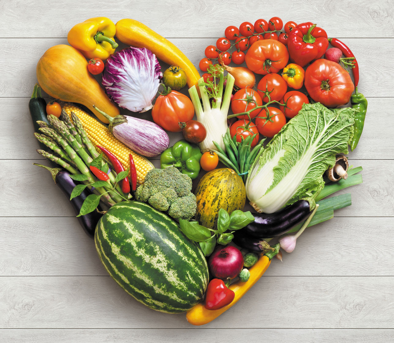 Heart symbol. Vegetables diet concept. Food photography of heart made from different vegetables on white wooden table. High resolution product.
